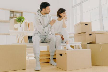 Indoor shot of frustrated woman and man face financial problems, sit on bench in empty spacious room, unpack cardboard boxes with personal stuff. Caring husband embraces wife with love, calms