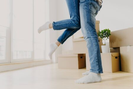 Happy unknown couple move in new abode, man lifts woman, wear jeans, pose in empty room with carton boxes around, start living seperate from parents rejoice buying apartment. Unrecognizable homeowners