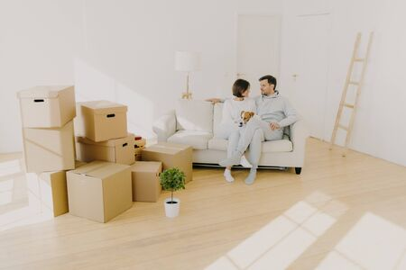 Happy young couple pose together on cozy sofa, have pleasant conversation, tease dog, relocate in new home, enjoy relax after unpacking personal belongings, stack of boxes near, house plant. Banco de Imagens
