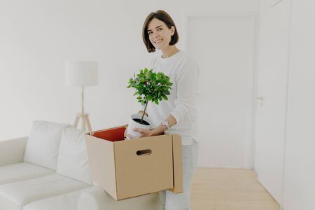 Pleased brunette young woman unpack belongings in carton box, holds green plant in pot, relocates in new apartment, dressed in casual clothes, stands in spacious room, being busy with house work