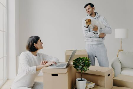 Happy family couple move into new flat for living. Wife works on laptop computer, searches information in internet, makes shopping online, man stands with dog, unpacks belongings from boxes.