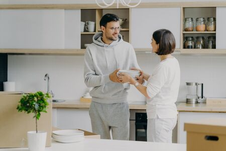 Photo of happy husband and wife unpack things after moving into new house, carry white plates, pose against kitchen interior, have fun, dressed in domestic clothes. People and moving concept