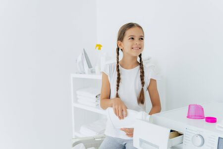 Little happy girl has two pigtails fills in washing machine with liquid detergent, pours into tray of washer, stands in laundry room with white walls, helps mother with washing, wears white t shirt Stock Photo