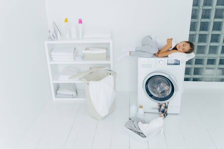 Shot of tired small kid sleeps on washing machine, uses white soft towel as pillow, has pleasant dreams, basket and basin on white floor, feels fatigue after loading clothes in washer, being at home