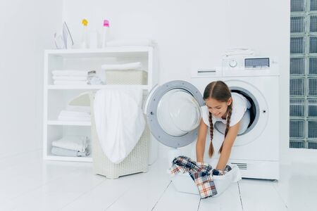 Pretty little girl householder poses inside of washing machine, takes checkered shirt from basin, engaged in laundry, has glad expression, two combed plaits. Childhood and washing day concept