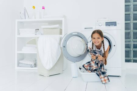 Positive kid with pigtails sticks out head from washing machine, has fun and holds shirt, prepares for washing, smiles gently, spends free time in laundry room. Children, cleanliness, hygiene concept Stockfoto