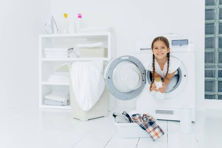 Small girl with appealing appearance, has fun and poses inside of washer, holds detergent, prepares for washing, basin with clothes for putting into washing machine on white floor. Laundry day at home