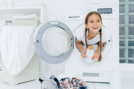 Happy European girl with two plaits, poses inside of wash machine, holds white bottle with liquid powder, has thoughtful expression, pile of dirty clothes in basin, looks somewhere into distance Stock Photo