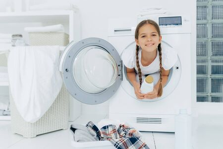 Smiling female child with glad expression, poses in washing machine, dressed in white t shirt, holds detergent, looks gladfully at camera, surrounded with much clothes and linen, does housework