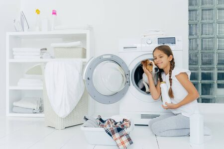 Photo of attractive girl petting pedigree dog in washing machine, holds washing detergent, going to load washer, busy with laundry and domestic chores, washes clothes at home, poses indoors.