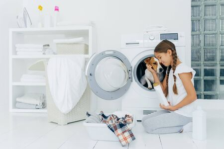 Small child plays with dog russell terrier, poses on knees near washing machine, busy with housekeeping and doing laundry, holds white bottle with washing powder, wears domestic comfortable clothes. Stockfoto