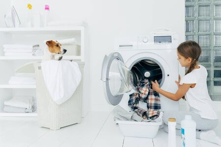 Busy child does laundry work, empties washing machine, cleaned clothes in basin uses detergents, little pedigree dog in basket. Modern household device at home. Female kid helps with family chores