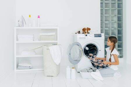 Housekeeping, children and domestic chores concept. Happy kid unloads washing machine, puts clean washed clothes in basin, curious dog looks from above, lies on washer in laundry room at home