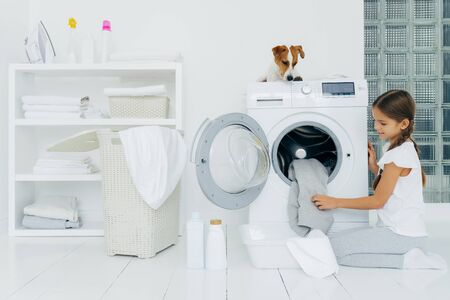 Busy little pretty girl does laundry at home, poses on knees near washing machine, uses liquid powder, pedigree dog on top of washer, looks at small female host householder. Housekeeping concept Stockfoto