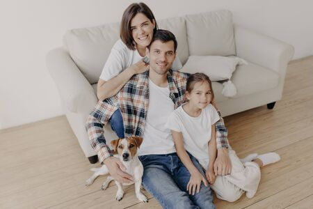 Top view of happy family members pose in spacious room near comfortable sofa, favourite dog poses near, enjoy spare time sit on floor, smile positively. Father, mother and child spend time at home