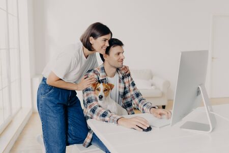 Happy wife in white t shirt and jeans, embraces husband who works at computer, helps him with making report, focused in monitor, domestic pedigree dog poses on owners knees. Working process.
