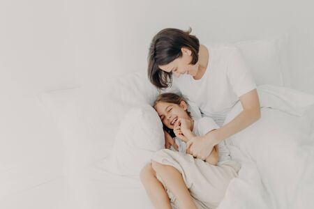 Top view of happy funny girl in pyjamas and her caring mom pose on bed, play together in bed, enjoy softness and comfort, express positive emotions. Family, morning time and relaxation concept Фото со стока