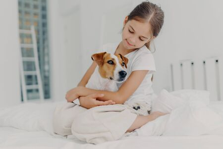Photo of relaxed beautiful small girl plays with pedigree dog, embraces favourite animal, dressed in casual pyjamas, sits on bed, expresses love to pet, poses in light bedroom. Happy childhood concept