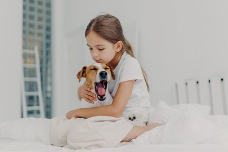 Fair haired small girl with pony tail wears casual pyjamas, embraces dog who yawns, pose together on comfortable bed, expresses love and care to domestic animal, spends morning weekend at home Stock fotó