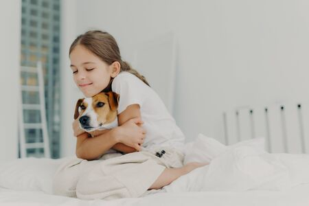 Pleased little girl plays with pet, embraces dog and keeps eyes closed from pleasure, dressed in nightclothes, poses on bed after waking up, expresses love to pedigree animal. Bedding concept