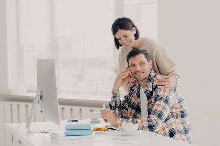 Caring woman helps her husband entrepreneur who has telephone conversation, tries to soleve working issues, writes information in notepad and works on computer. Family couple manage finances