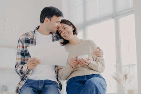 Indoor shot of relaxed beautiful woman with coffee cup, receives hug from husband who holds papers, make financial report together, own business company. Family, finances and budget concept.