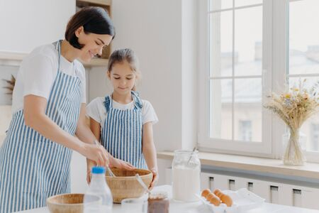 Photo of brunette woman in striped apron, mixes ingredients with beater, shows small daughter how to cook, stand at kitchen near table with fresh products. Mother and child busy preparing meal