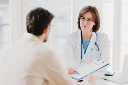 Female general practitioner explains which prescribed medicine patient should buy, gives medical visit consultation. Male clinic visitor tells about health complaints to therapist. Healthcare concept