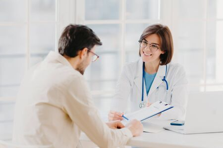 Woman doctor with stethoscope holds binder with patient personal medical card, consults patient who has medical problems, sit at hospital office, discuss medical checkup results, offers insurance