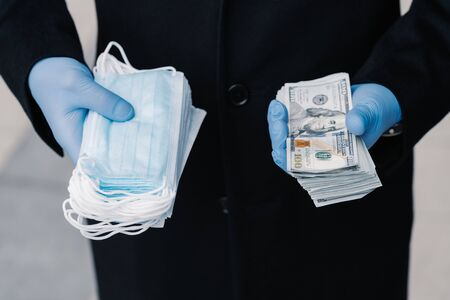 Increasing prices on medical masks durig spread of coronavirus epidemic. Person in protective medical gloves holds stack of masks and much money. Profitable business, speculation during quarantine.