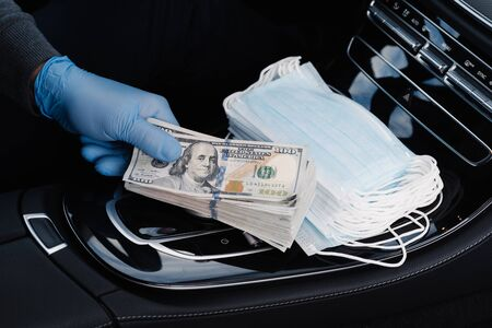 Virus concept. Hand in rubber gloves holds stack of dollar banknotes, earns money as sells medical masks, poses in car. Covid epidemic. Speculation at market of necessary products. Quarantine period Archivio Fotografico