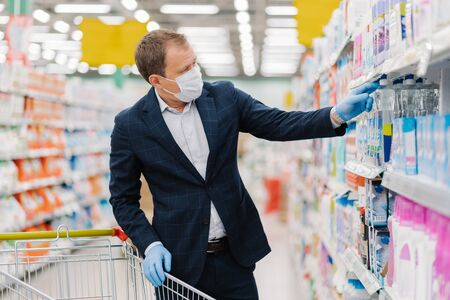 Image of man consumer buys detergent in shopping mall, takes bottle of washing gel in cart, chooses household products, cares about hygiene and protection during pandemic situation, virus spread