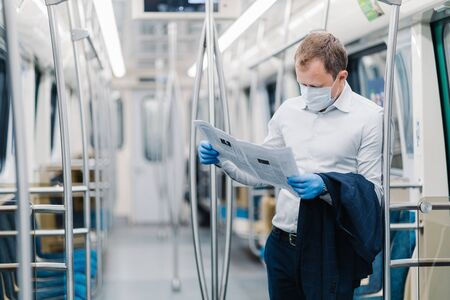Horizontal shot of adult man wears formal clothes, protective medical mask and gloves, reads press, finds out news during virus outbreak, commutes to work in public transport. Coronavirus, Covid-19