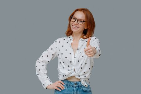 Pleasant looking confident woman with ginger hair, shows thumb up, says very good and encourages friend, likes someones idea, gives positive reply, wears stylish outfit, stands indoor over grey wall Banque d'images