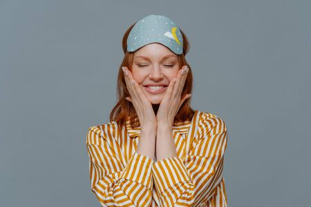 Pleased woman touches cheeks, has healthy freckled skin, smiles broadly prepares for sleep, wears striped pajama and sleep mask, closes eyes, isolated over grey background. Rest and lifestyle concept