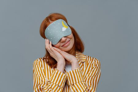 Pretty redhead woman wears blindfold on eyes, keeps hands pressed together near face, sees pleasant dreams while sleeping, dressed in domestic clothes, isolated on grey wall, feels comfortable