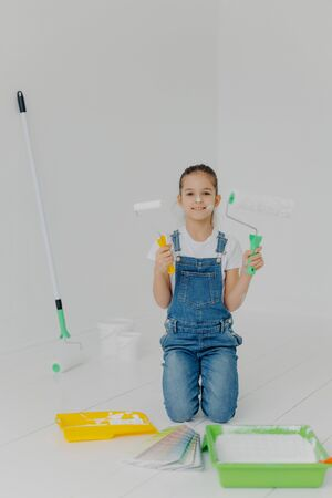 Happy little girl in denim overalls stands on knees, holds paint roller, surrounded with trays with paint, poses in white room, has happy expression, helps parents with house improvement and painting Foto de archivo