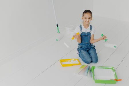 Top view of small European girl in denim overalls stands on knees, uses paint rollers, helps parents with house remodeling, poses on floor, chooses colors on samples, has cheerful expression