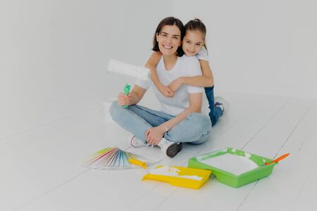Indoor shot of happy woman gets warm hug from lovely daughter, pose together in empty room, choose bright color for painting from sample palette, busy with house renovation ande redecoration.