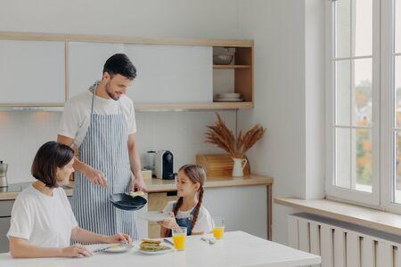 El padre preparó huevos fritos para la familia, el niño pequeño sostiene el plato y espera el desayuno. La familia posa en la cocina junto a la mesa, disfruta de una comida sabrosa, tiene expresiones alegres. Gente, comida, ambiente doméstico. Foto de archivo