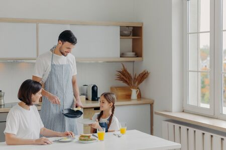 Father prepared fried eggs for family, little child holds plate and waits for breakfast. Family pose at kitchen near table, enjoy tasty meal, have glad expressions. People, eating, domestic atmosphere 版權商用圖片