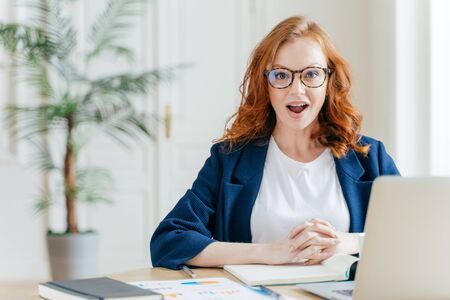 Surprised ginger female employee has job, develops new business srategy, poses in front of opened laptop computer, poses in workspace against office interior. Woman software developer at work.