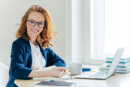 Self confident young female director plans work process, writes main theses in notepad, rewrites information from laptop computer, drinks tea, poses over office interior. Technology, occupation