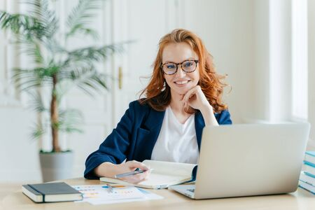 Photo of successful ginger female freelancer has remote work, watches webinar online on laptop computer, writes down information in notepad, smiles happily poses at workplace dressed in formal clothes