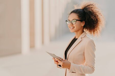Profile shot of glad dark skinned woman with Afro hair, dressed elegantly holds tablet computer in hands strolls at street wears optical glasses connected to high speed internet. Lifestyle, technology Stock Photo