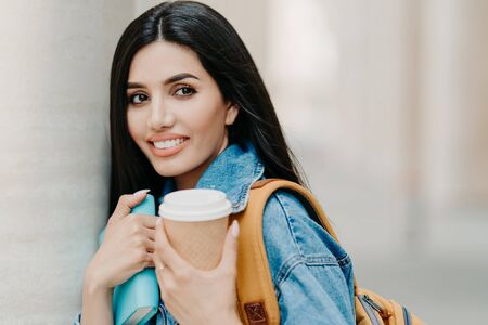 Outdoor shot of brunette female student with makeup, dark long hair, dressed in denim jacket, holds takeaway coffee, textbook, carries rucksack, looks somewhere into distance, strolls in city