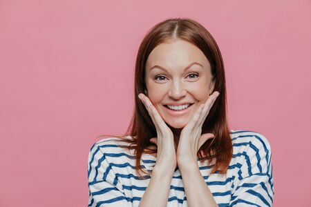 Headshot of attractive young woman touches cheeks with both palms, has sincere smile, wears casual white and blue striped sweater, isolated over pink background with free space for your text Фото со стока