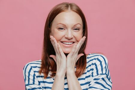 Photo of attractive European young woman has gentle smile, shows white teeth, touches cheeks with both palms, wears casual clothes, expresses sincere feelings, isolated over pink background.