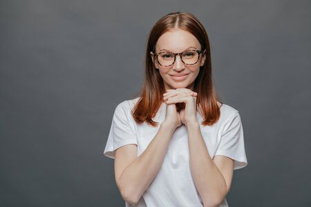 Joyful pleasant looking lady keeps both hands under chin, smiles positively at camera, wears optical glasses, casual t shirt, enjoys spare time in good company, isolated over grey background