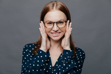 Photo of attractive woman with pleased facial expression, keeps both hands near cheeks, wears polka dot shirt, poses over grey studio wall, being happy. European pleased lady expresses happiness Фото со стока